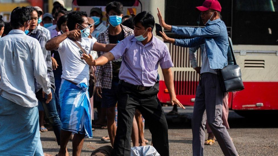 A military supporter points a sharp object as he confronts anti-coup protesters in Myanmar