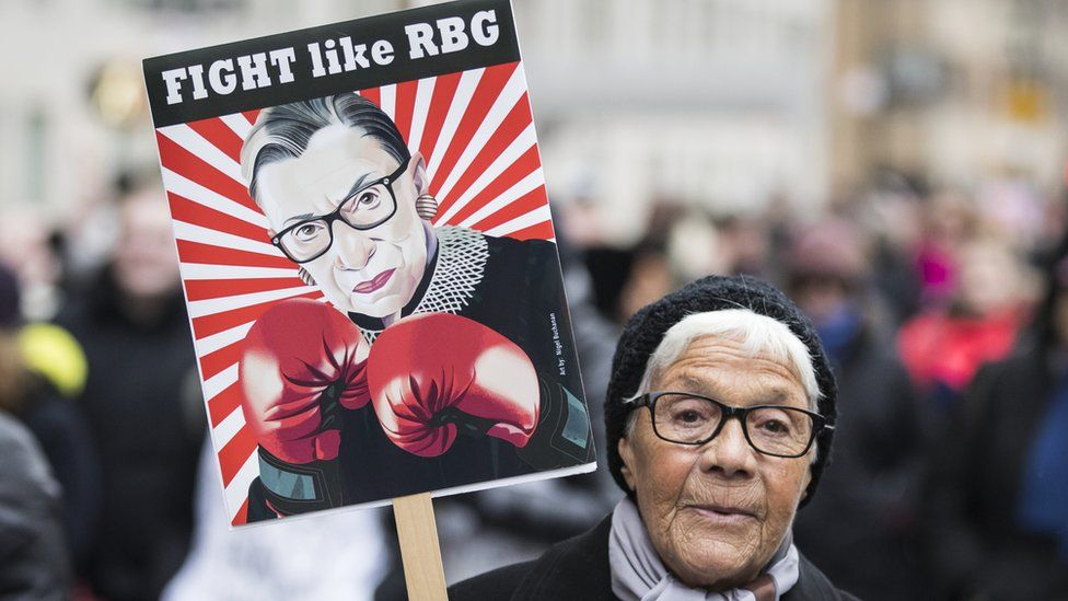 An older marcher holds a sign that says 'Fight like RBG' with a picture of Ruth Bader Ginsberg