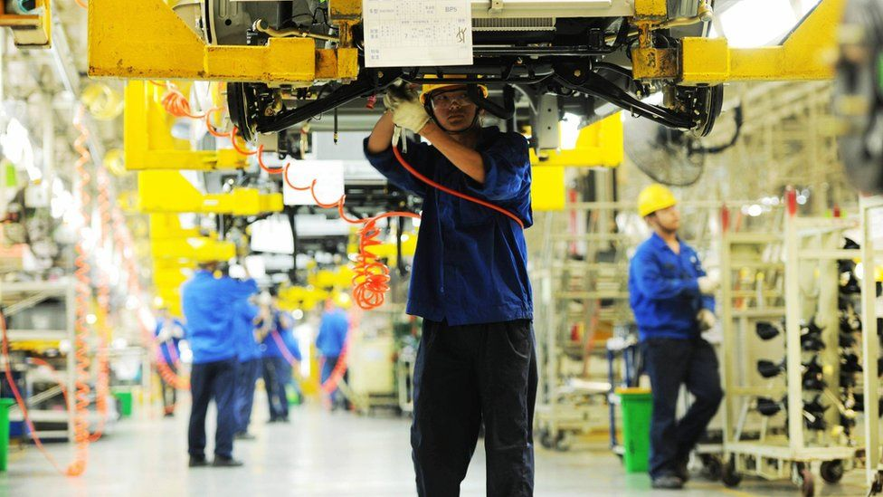 Workers install car parts at their assembly line in a factory in Qingdao, China