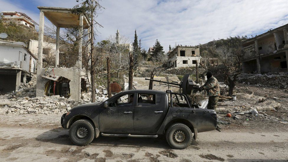 Forces loyal to Syrian President Bashar al-Assad drive a vehicle in the town of Rabiya (27 January 2016)