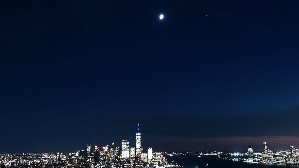 The moon, Saturn and Jupiter form a triangle as they rise over lower Manhattan and One World Trade Center