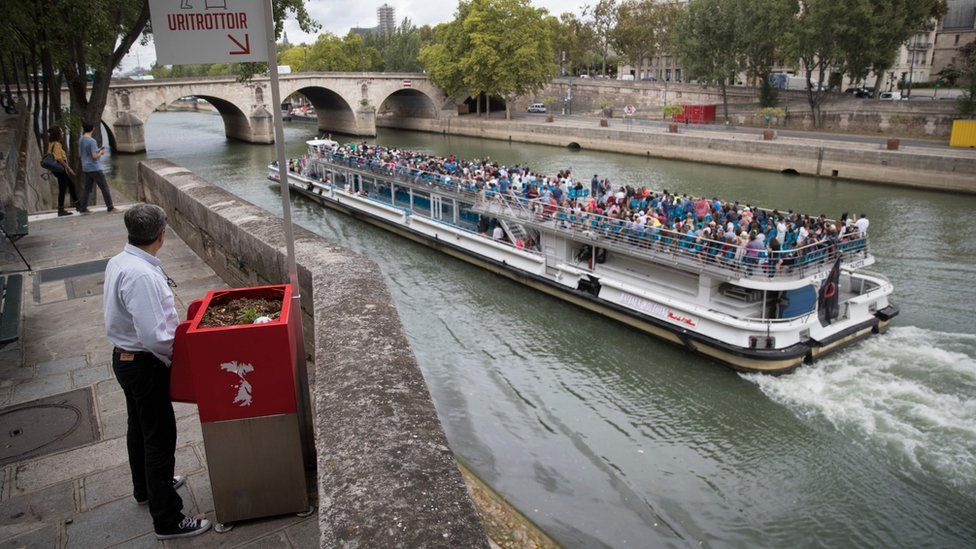 """A man stands at a """"uritrottoir"""" public urinal on August 13, 2018, on the Saint-Louis island in Paris"""