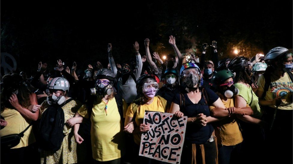 A group of mothers stands between protesters and federal officers in Portland