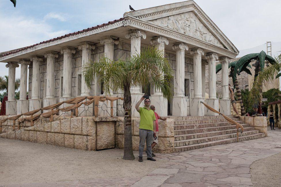 A man takes a selfie outside a Roman style building