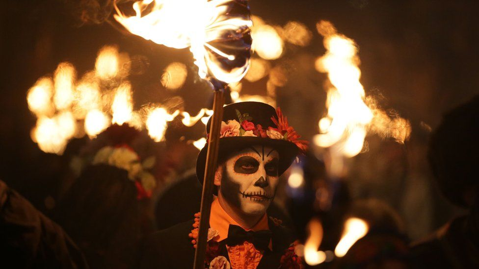 Man with skull face paint carrying a torch