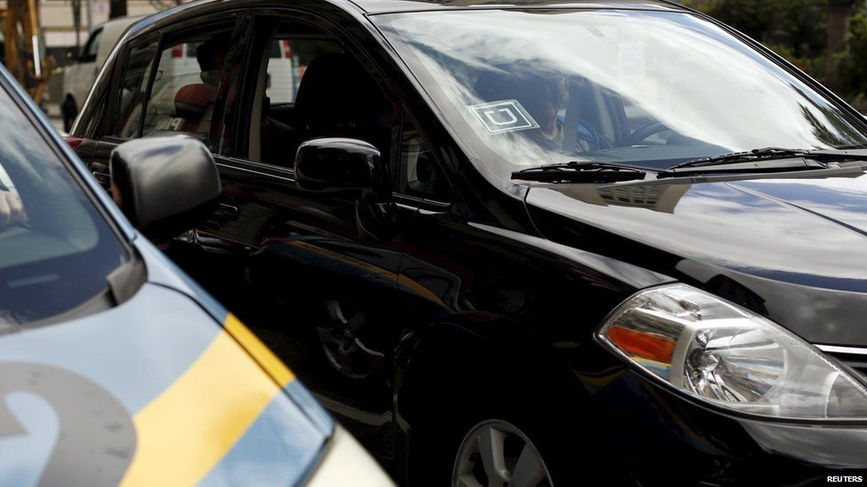 The Uber logo is seen on a vehicle next to a taxi near Union Square in San Francisco