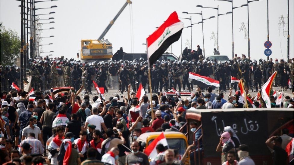 Iraqi security forces stand in front of demonstrators during a protest over corruption, lack of jobs, and poor services, in Baghdad, Iraq October 25, 2019