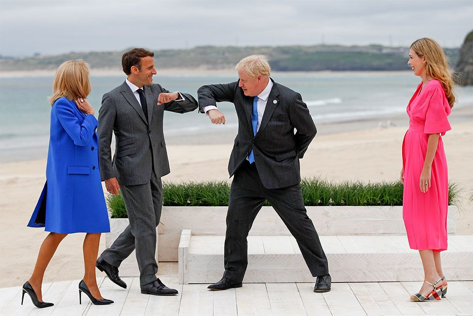 Prime Minister Boris Johnson greet France's President Emmanuel Macron with an elbow bump as their spouses look on in Cornwall, during the G7 summit