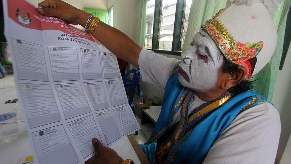 Java election official with ballot paper
