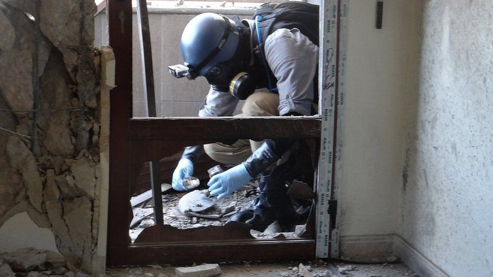 A UN expert collects samples at a site where rockets filled with Sarin hit a suburb of Damascus, Syria (29 August 2013)