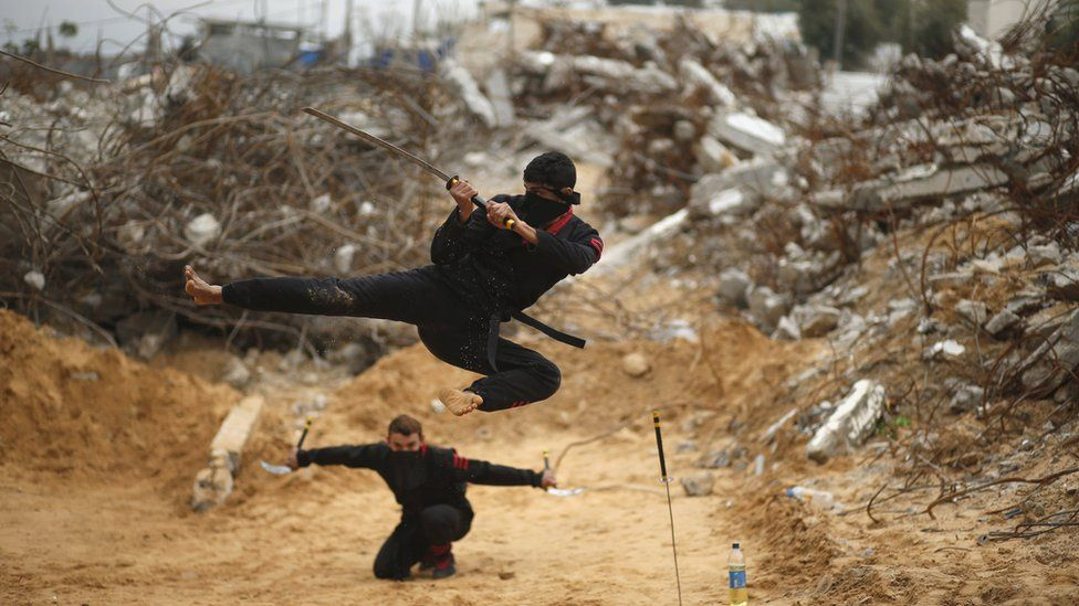 Palestinian youths demonstrate ninja-style skills in front of the ruins of buildings in Gaza, destroyed in the 2014 war