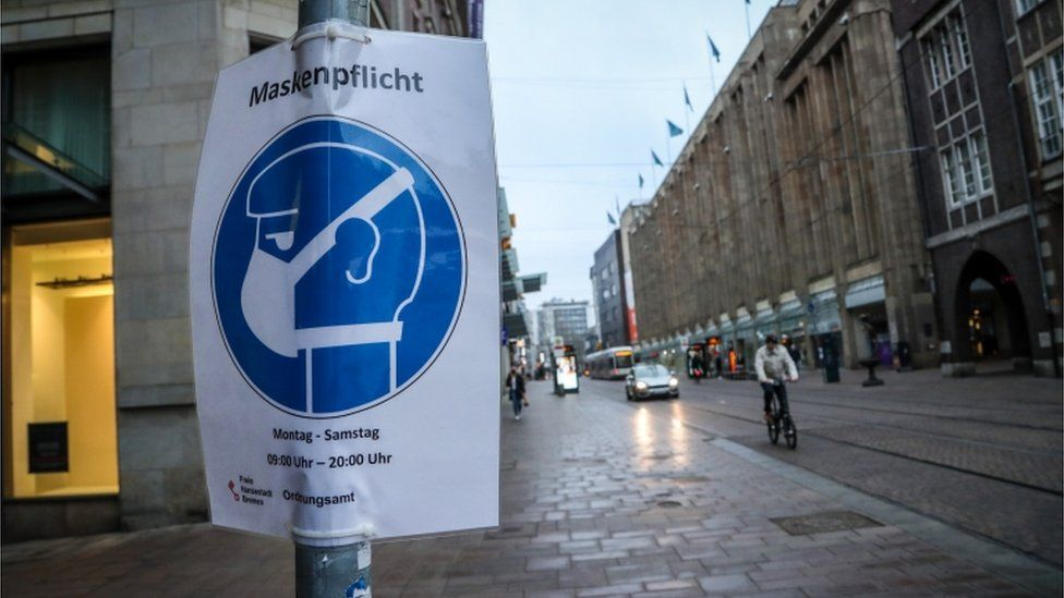 A sign indicating that face masks are mandatory hangs from a pole in the city centre of Bremen, Germany
