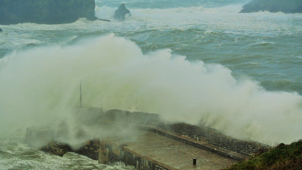 Waves crashing over Mullion harbour in Cornwall