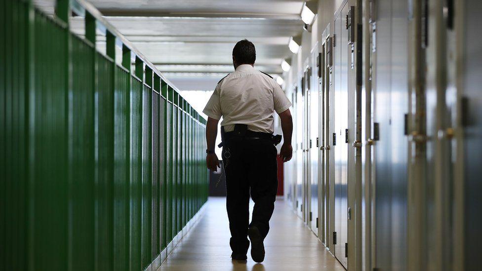 A prison guard walks along a corridor in HMP Berwyn