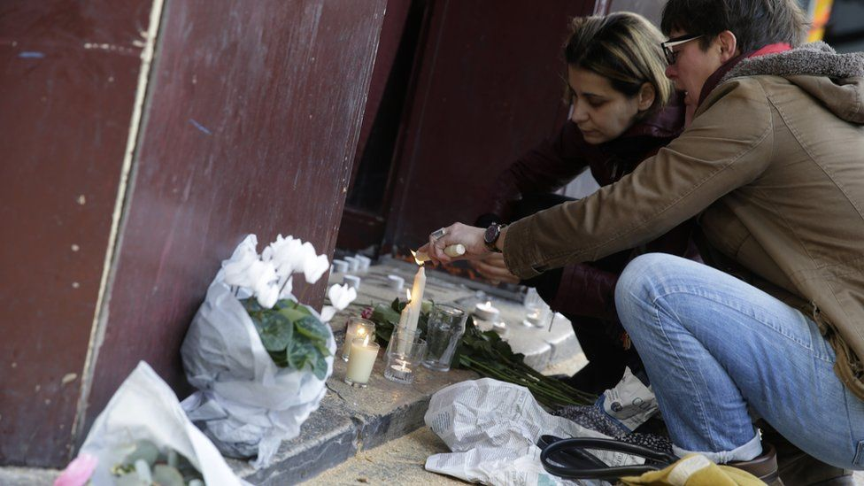 People leave flowers and light candles outside of the Carillon bar in the 10th district of Paris on November 14, 2015