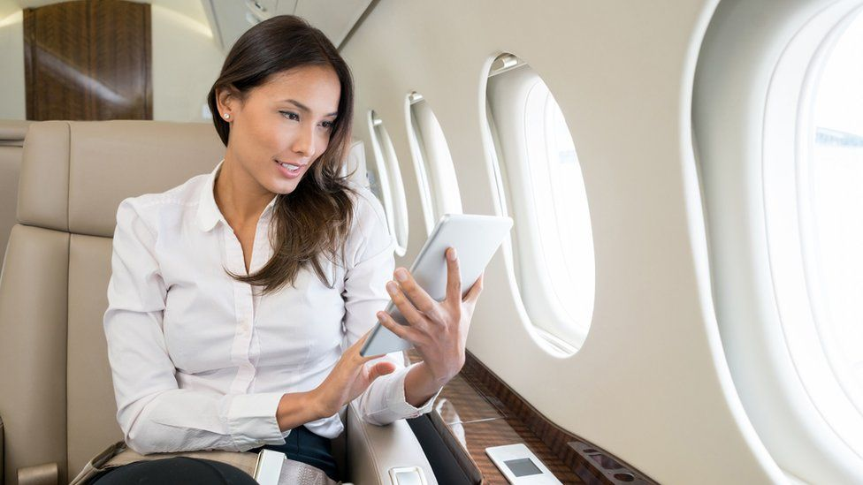 Woman on jet checking her tablet