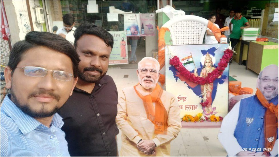 Mayank Patel celebrating and posing with the statue of Narendra Modi and Amit Shah.