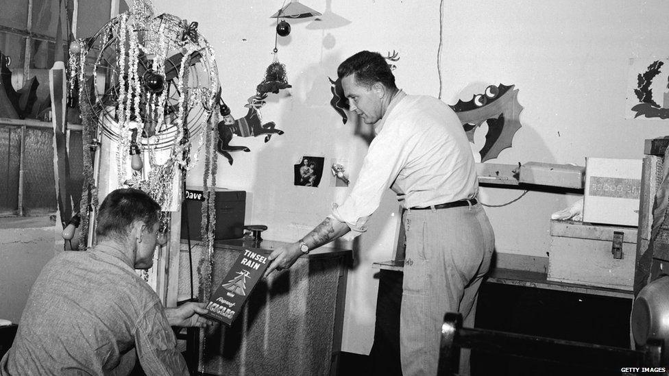 Two men decorating a prison