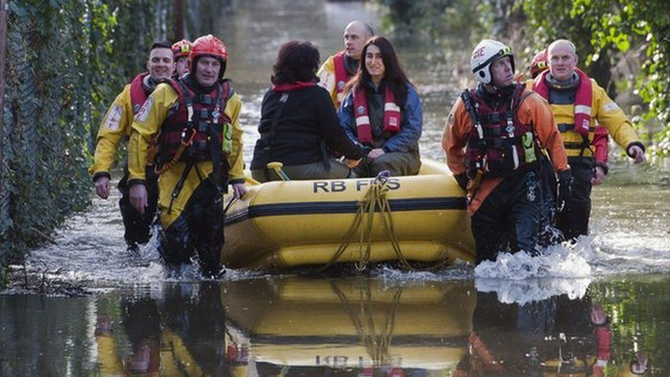 Fire and rescue crews rescue residents whose houses have been flooded in Staines-upon-Thames