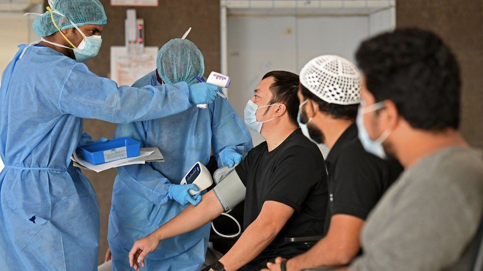Migrant workers have their temperature and blood pressure checked by medics before leaving a medical facility in Dubai (22 April 2020)
