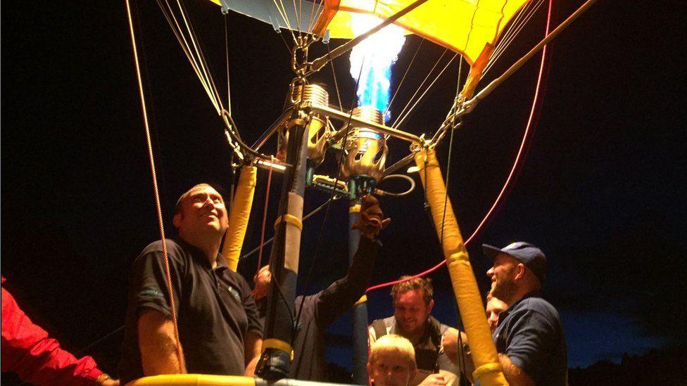 Pilot in balloon operates burner
