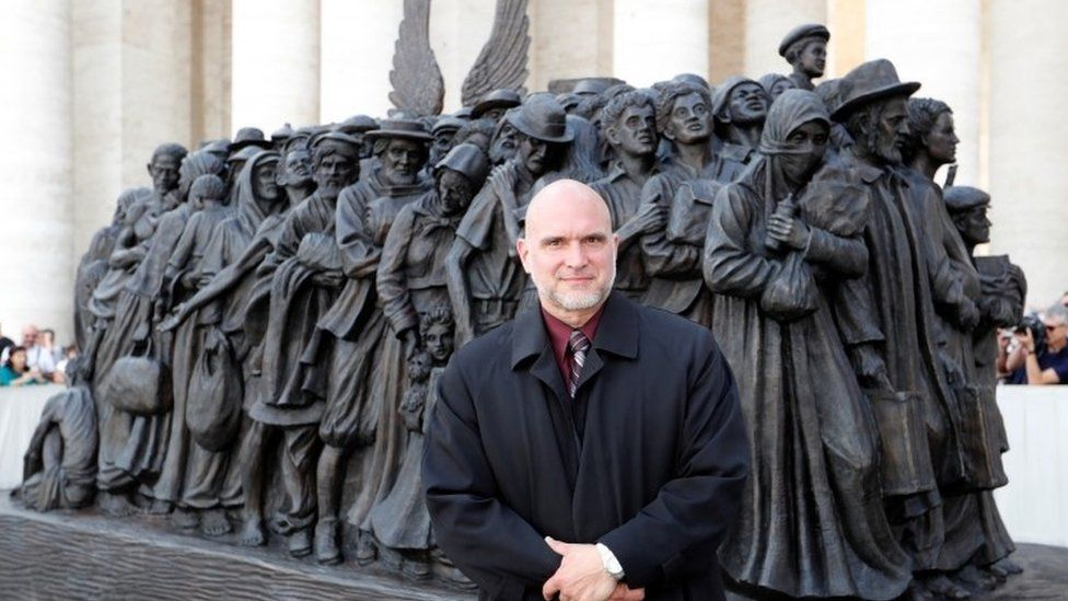 Timothy P. Schmalz stands in front of the sculpture