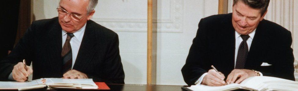 Reagan and Gorbachev Signing Arms Limitation Agreement at a table in front of their nations' flags.