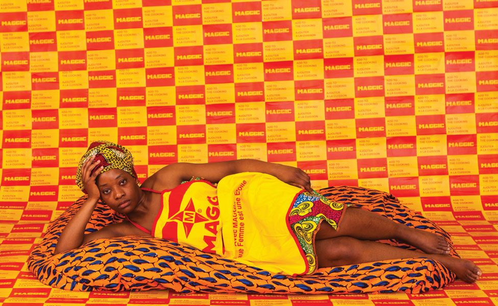 A woman lies on a soft blanket, looking into the camera, wearing Maggi stock cube branded dress, behind her a wallpaper made of the Maggi logo