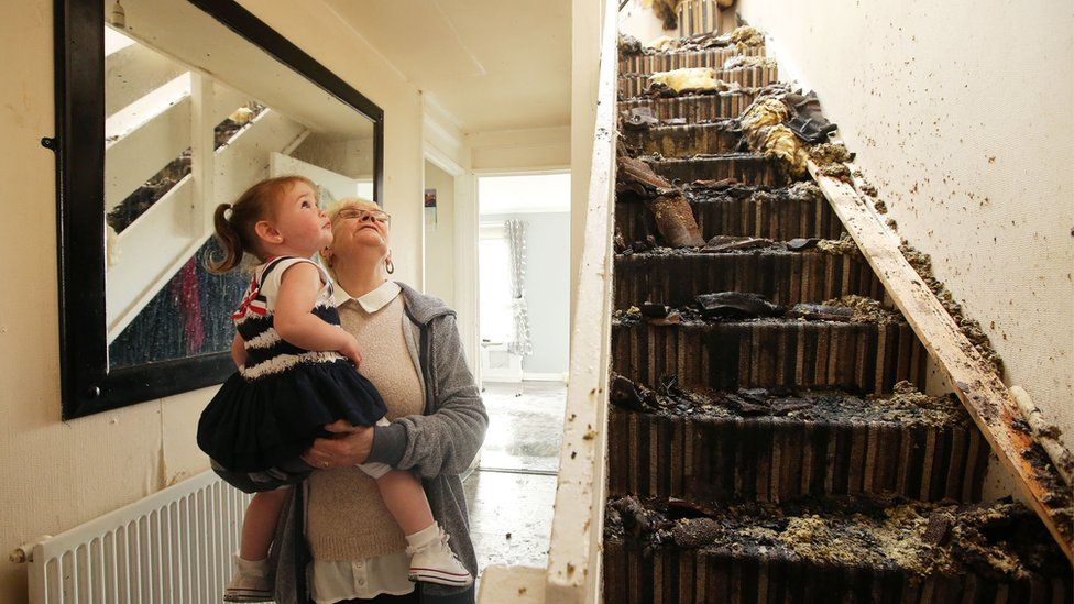 Lily Turtle and her grand-daughter Skyla Hogg look at the damage done to her house