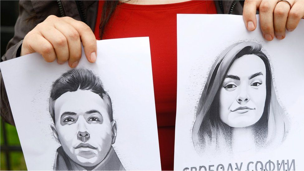 A woman holds a portrait of opposition journalist Roman Protasevich and his girlfriend Sofia Sapega during a protest of solidarity with Roman Protasevic at the Belarusian embassy in Riga, Latvia, 25 May 2021.