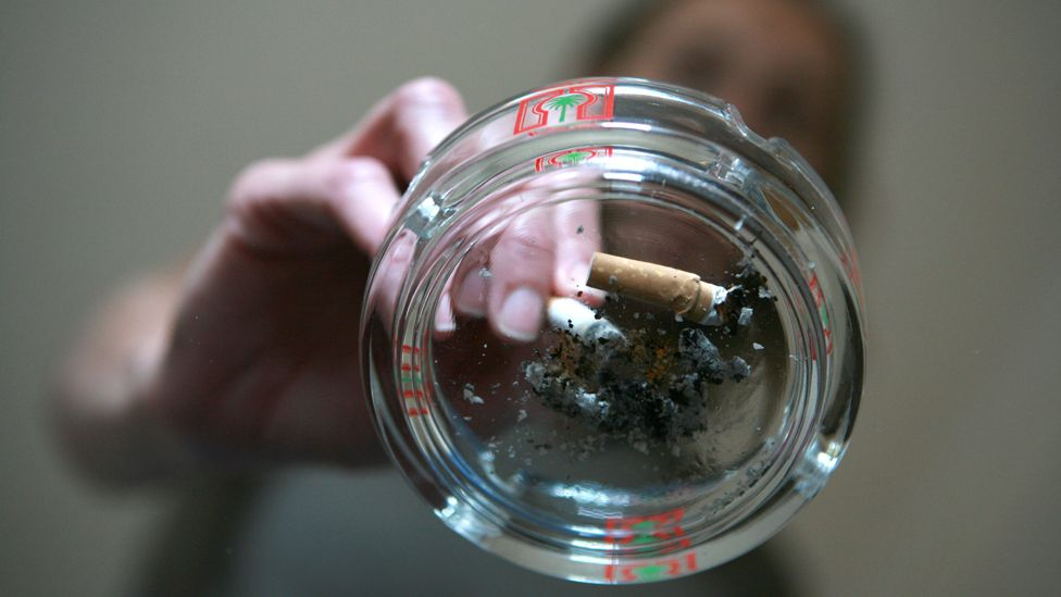 Smoker extinguishes a cigarette into a used ashtray on top of a glass coffee table