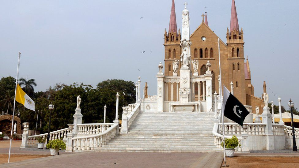 The flags of Vatican City and Pakistan flying at half mast outside the church