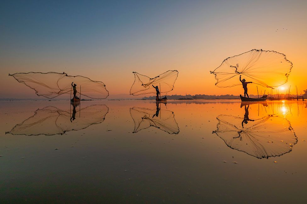 Three fisherman throwing their nets out to sea with a sunset behind them