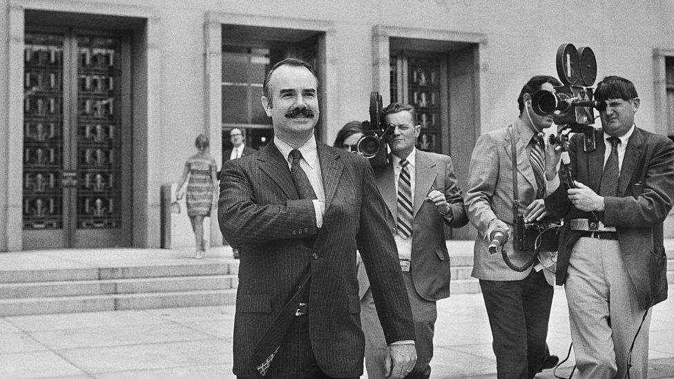 Former White House aide G Gordon Liddy is filmed by journalists as he leaves US District Court, where he pleaded Not Guilty of breaking into Democratic National Headquarters at the Watergate Hotel