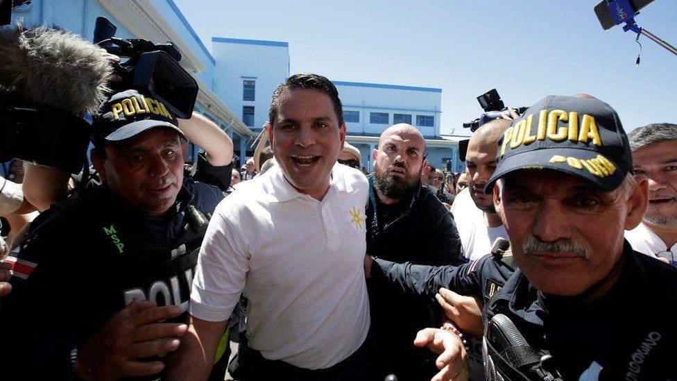 Fabricio Alvarado Muñoz, escorted away by police after casting his vote in February