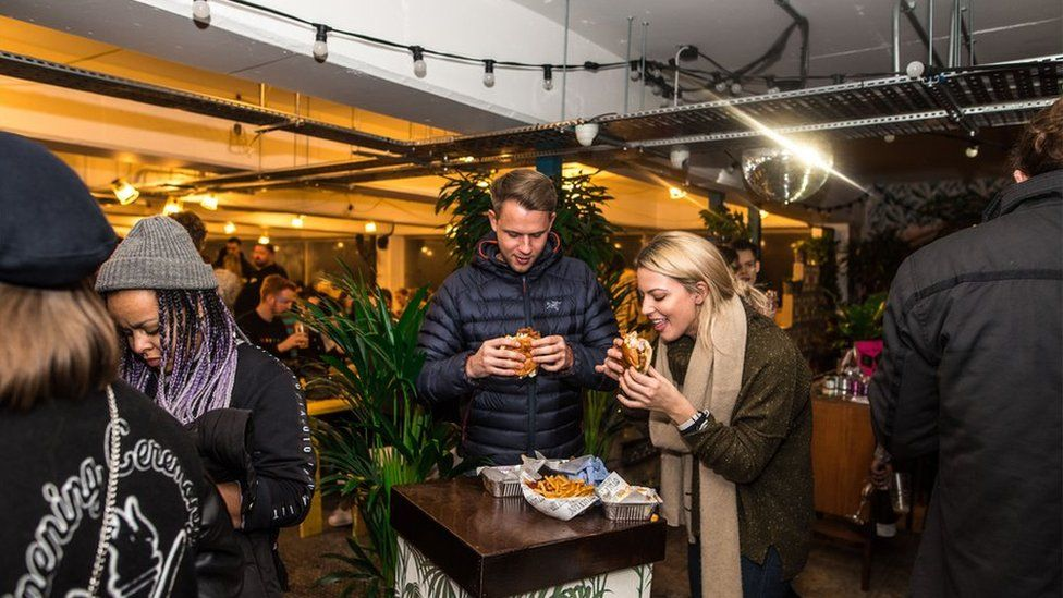People eat street food at a food court in Peckham Levels