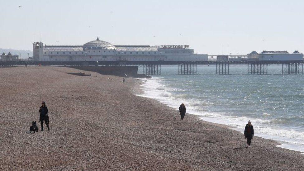People walk along Brighton beach on Sunday 5 April