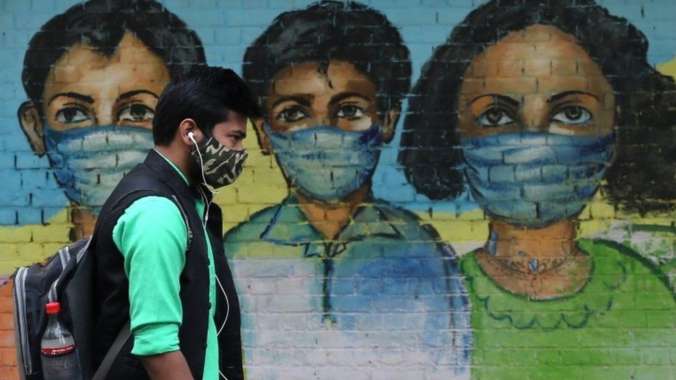 An Indian man passes by a mural on a wall to spread awareness about wearing a protective face mask to avoid spread of novel coronavirus in New Delhi, India, 07 November 2020.