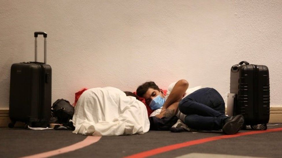 Tourists rests on the floor of the Cancun Convention Center, turned into an evacuation center, ahead of the arrival of Delta hurricane, in the touristic city of Cancun, Quintana Roo state, Mexico, late 06 October 2020