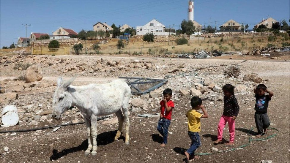 Palestinian children play near a donkey in Um al-Kheir in front of Israeli settlement of Maon (14/06/20)