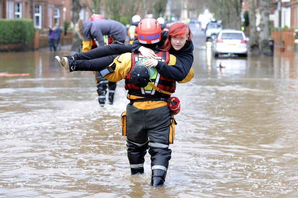 A woman is carried to safety by a rescue worker in Carlisle