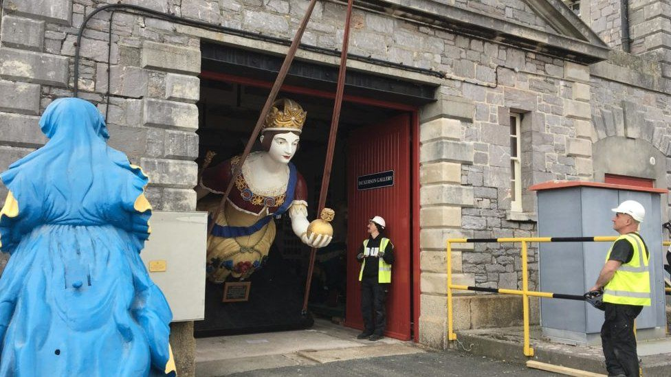 Figurehead of a queen leaving a workshop