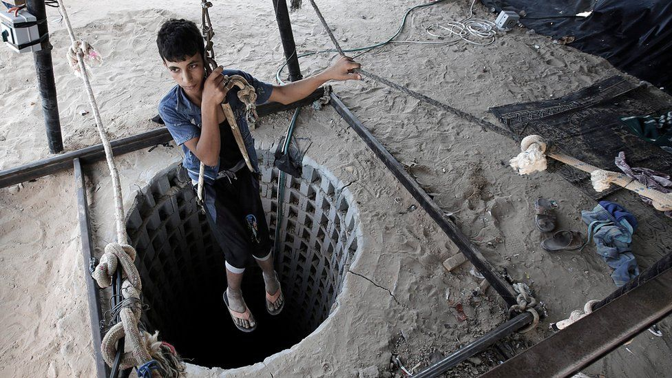 A Palestinian youth descends into one of the tunnels on the Gaza side of the border with Egypt in Rafah (19 September 2015)