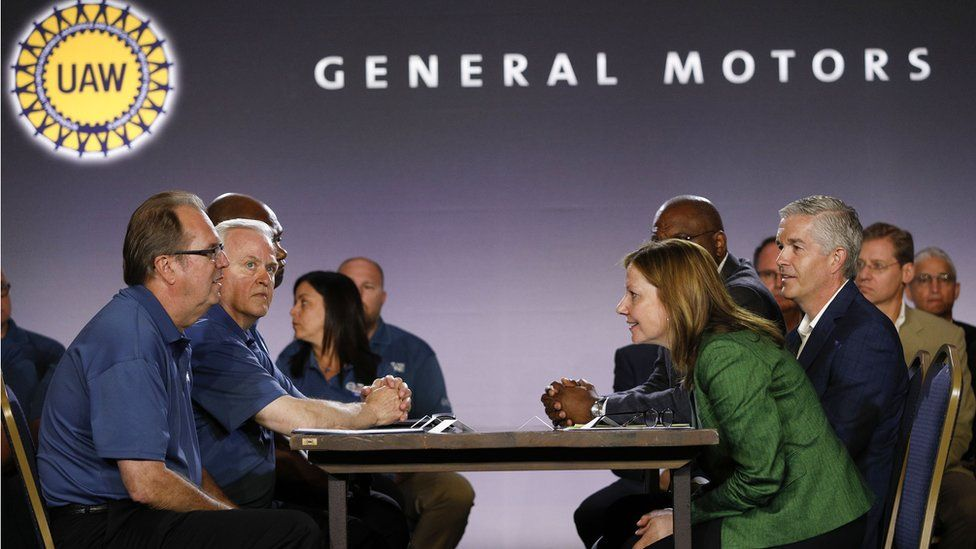 General Motors CEO Mary Barra sitting across from leaders of the United Auto Workers union