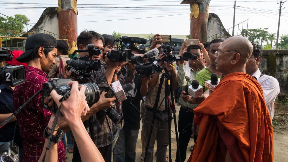 A Buddhist monk in orange robes addresses a gaggle of journalists on the monastery grounds in Maungdaw