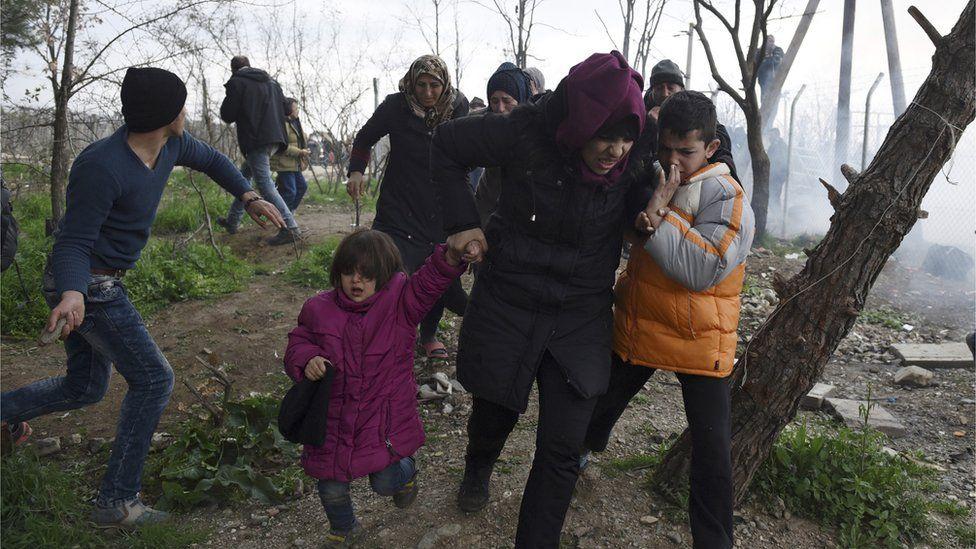Migrants fleeing tear gas on border, 29 Feb 16