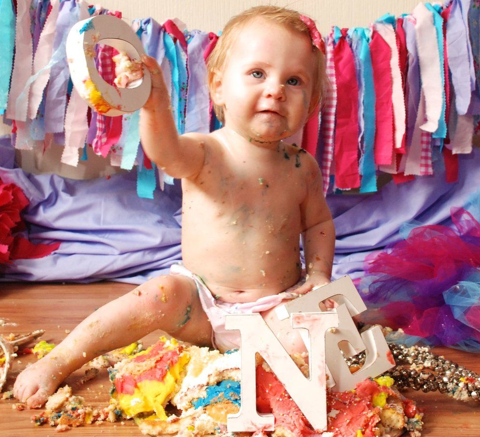 Baby Alanis holding up a letter O, from those displayed on her ONE birthday cake