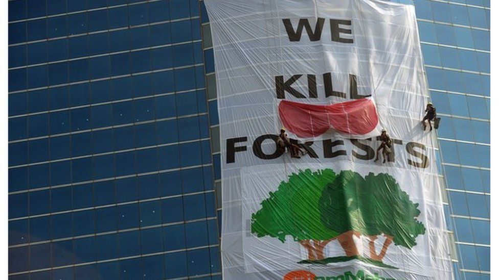 Activists from the environmental group Greenpeace drape the headquarters of India's Essar Group with a giant banner during a protest in Mumbai on 22 January, 2014