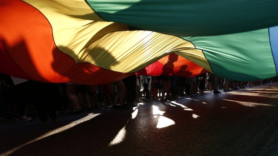 People hold a giant rainbow flag as they participate in the annual gay pride parade in Athens, Greece, 11 June 2016