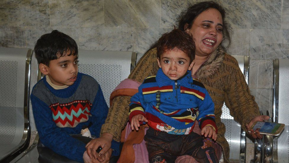 A woman cries as she sits with two young boys, one bloodstained, on a bench, following the attack in Quetta (December 17, 2017)